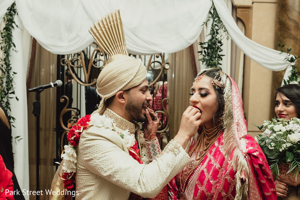 Indian bride and Indian groom feeding a cookie to each other