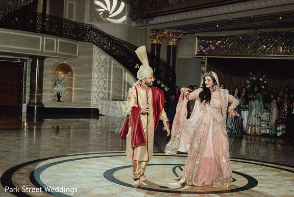 Indian newlywed couple dancing at the reception hall