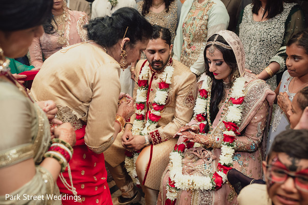 Indian newlywed couple surrounded by their Indian relatives
