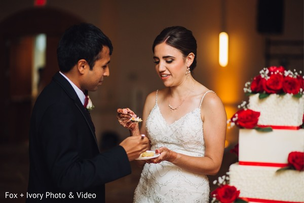 Indian bride and groom sharing a slice of cake during the reception.