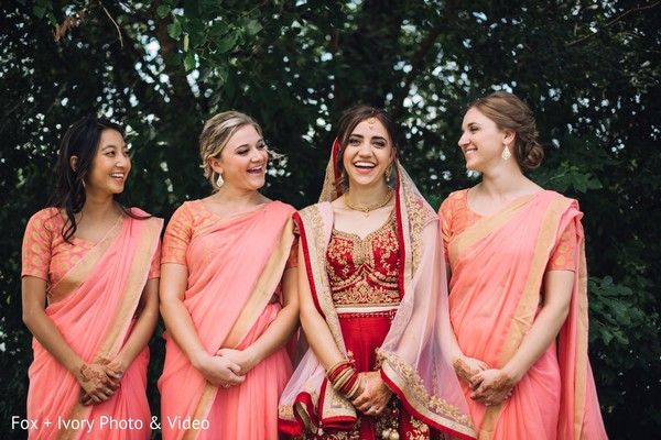 Indian bride posing with her beautiful bridesmaids outdoors.