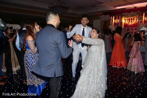Indian bride and groom dancing during the reception.