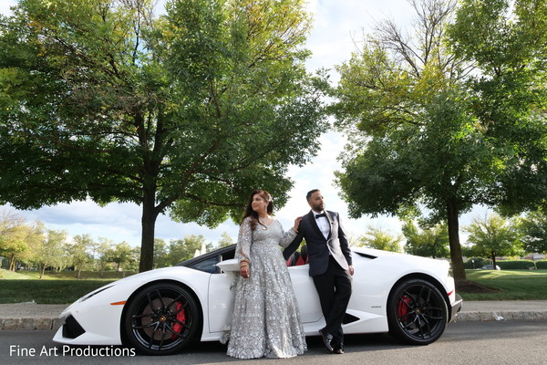 Indian bride and groom posing for pictures by the car.