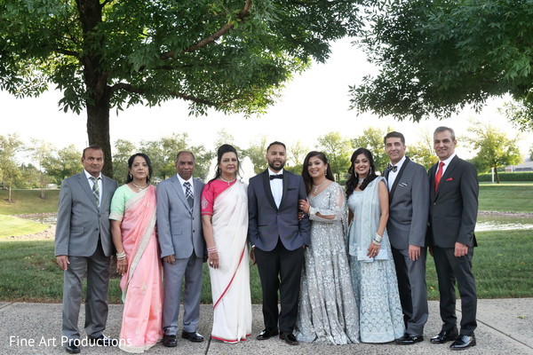 Indian groom and bride posing with special guests.