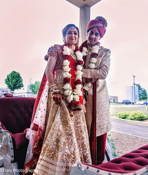 Indian bride and groom in an open carriage.