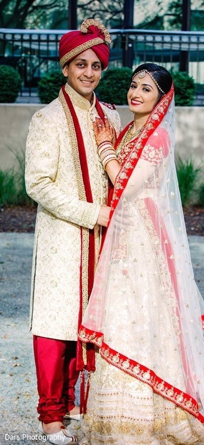 Indian couple in matching beige and gold wedding outfits.