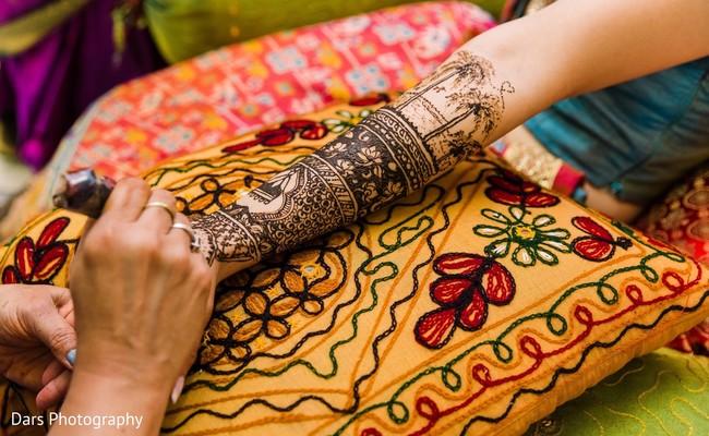 Indian mehndi artist making dark henna art on maharani's hands.