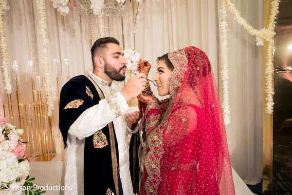 Indian newlyweds feeding each other cake