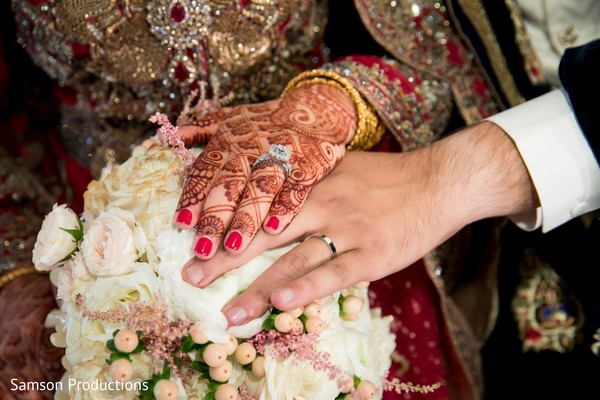 A close up to the hands of the Indian newlyweds over the buquet