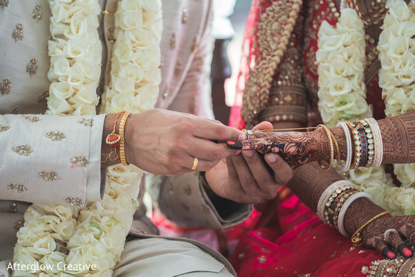 Closeup capture of Indian groom putting ring to bride.