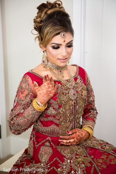 Maharani in red and gold showing her henna stained hands