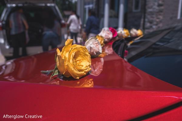Yellow rose decorates red Indian wedding vehicle.