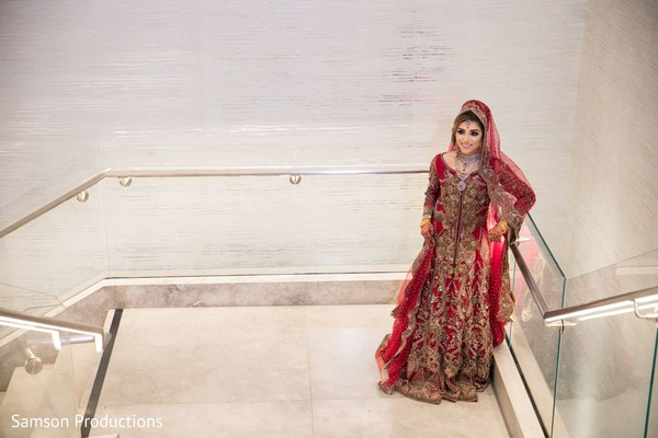 Maharani in red and gold posing on the stairs