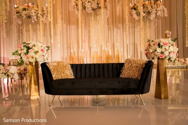 The couch on a stage decorated with flowers
