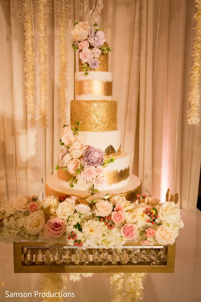 The wedding cake decorated with flowers and gold