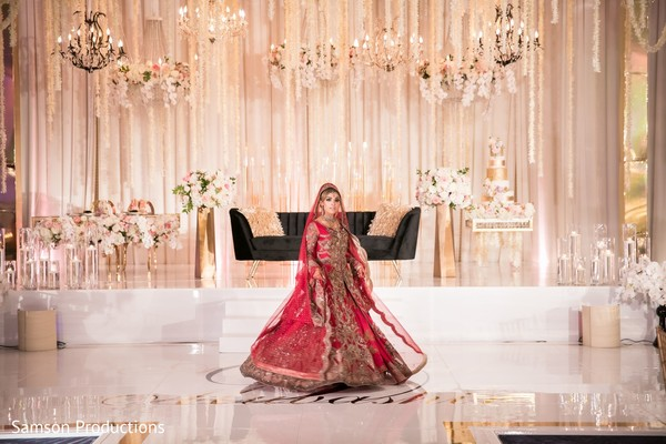 Maharani in red and gold in front of the reception stage