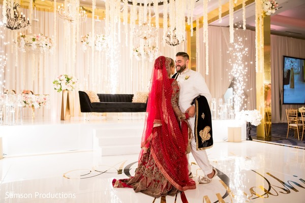 Indian newlyweds smiling together in front of the reception stage