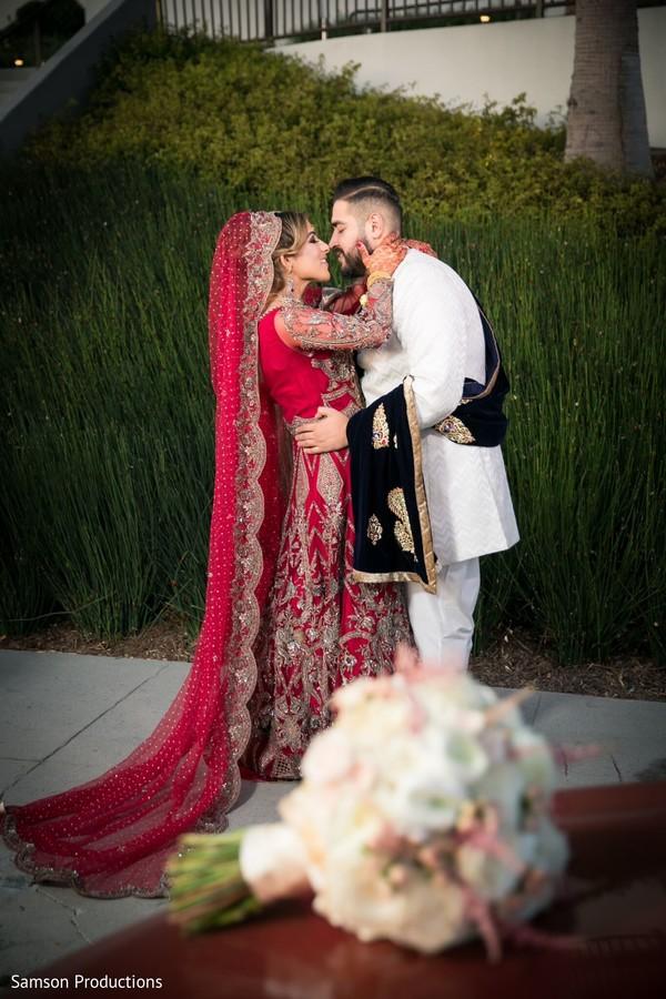 Indian newlyweds kissing outside the wedding venue