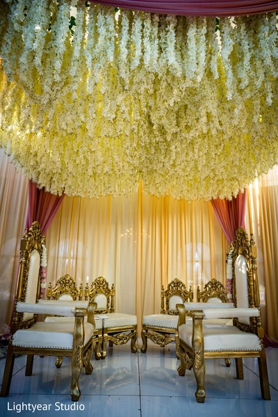 White flowers hanging from the mandap ceiling.