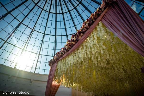 Cream color flowers hanging from the mandap.