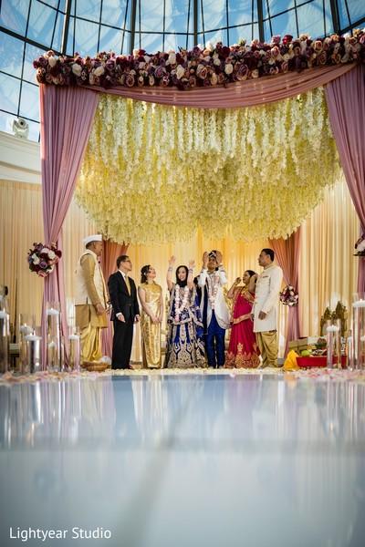 Indian bride and groom under a big floral mandap.