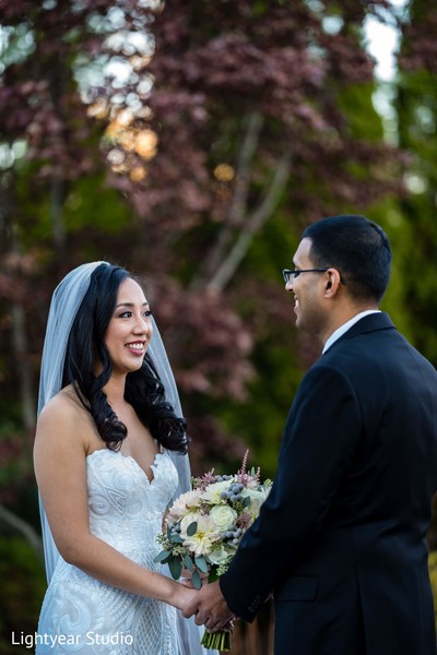 Indian bride with groom holding white and green bouquet.