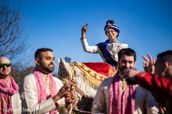 Indian groom riding on his white baraat horse