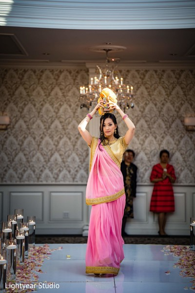 Indian bridesmaid walking on ceremony aisle with jar on head.