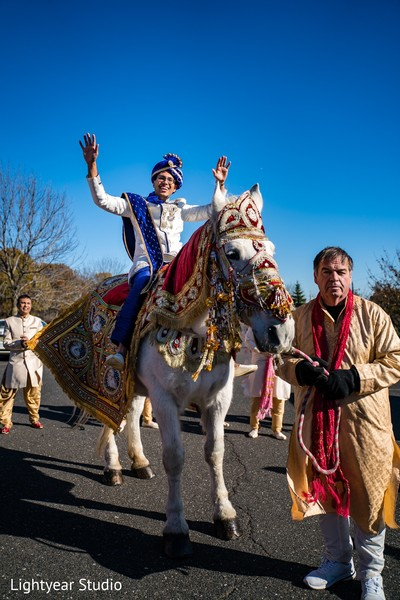 Indian groom riding his white baraat horse.