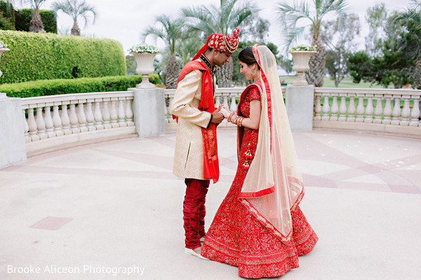 Indian couple in wedding attires posing for photo.