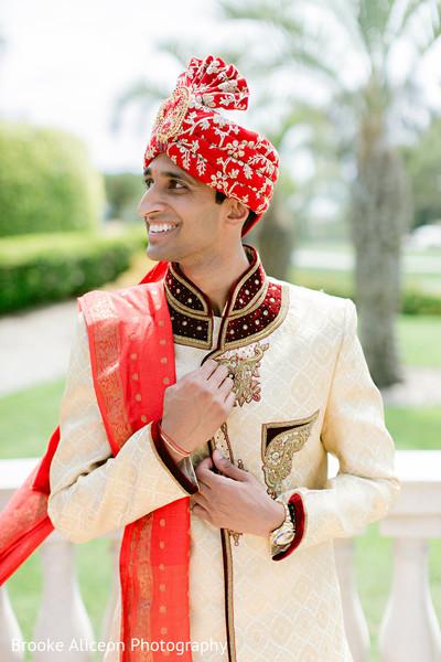 Indian groom adjusting his sherwani.