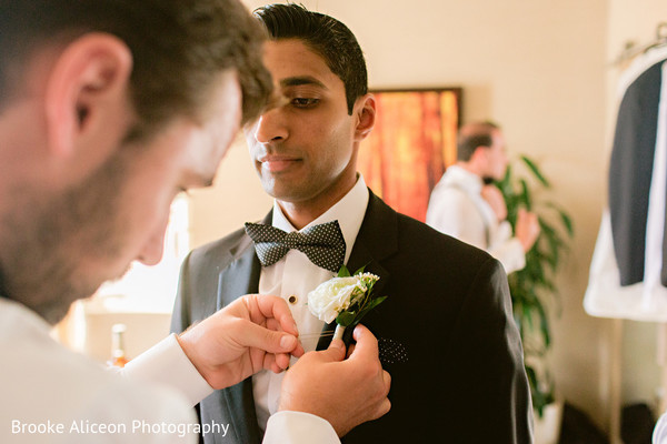 Indian groom being assisted with boutonniere.