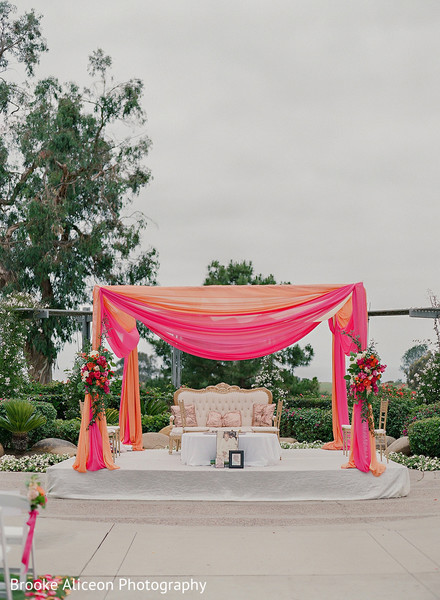Hindu wedding altar decorated with drapes and flowers.
