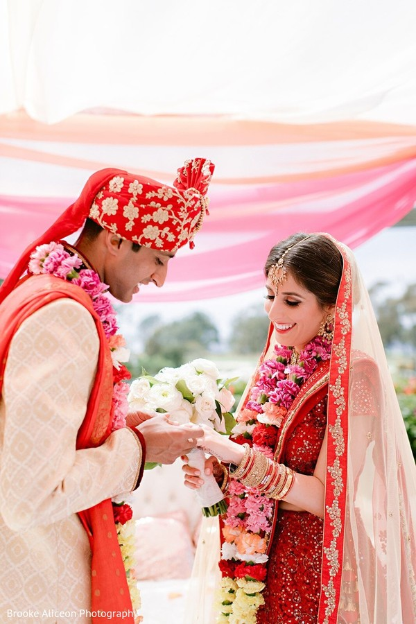 Indian groom putting wedding ring on her maharani's hand.
