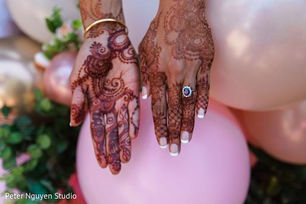 Indian bridal mehndi art decoration on her hands.