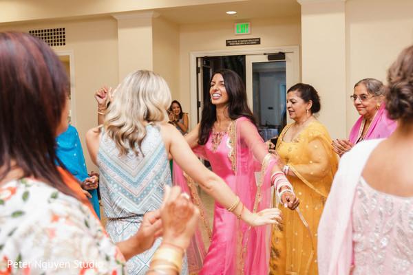 Indian bride dancing on her pink Straight Cut Salwar Kameez.