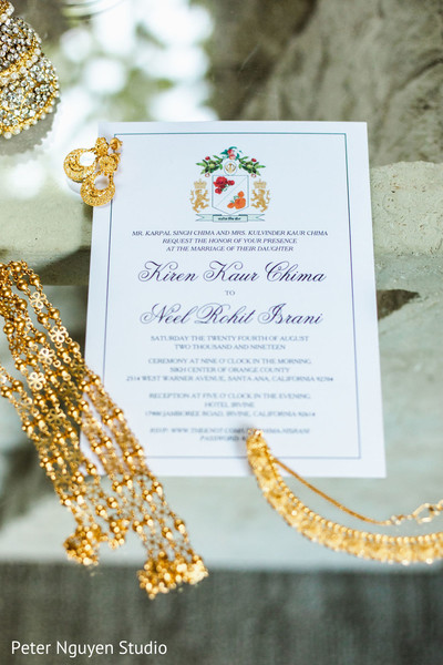 Indian wedding invitation and yellow gold jewelry.