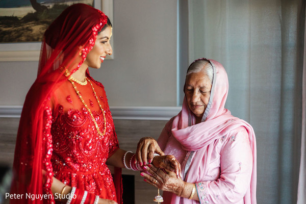 Indian bride getting on her kalire from relative.