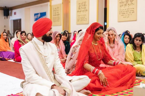 Indian couple sitting on the floor at wedding ceremony.