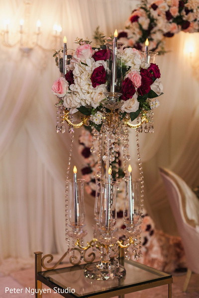 Indian wedding reception table chandelier with flowers decoration.