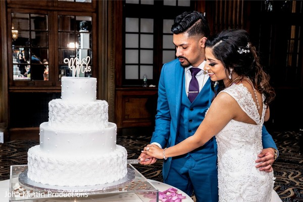 Indian couples cutting cake moment.