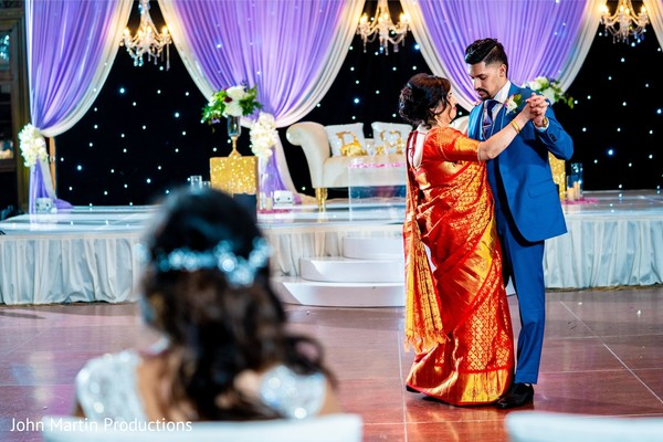 Indian groom dancing with mother at reception capture.