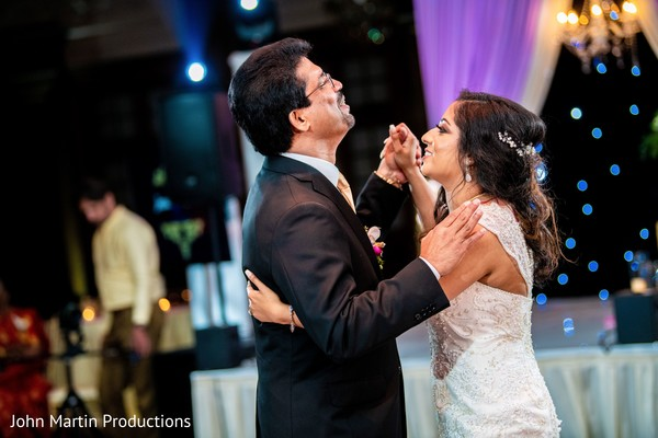 Indian bride dancing with her father at reception.