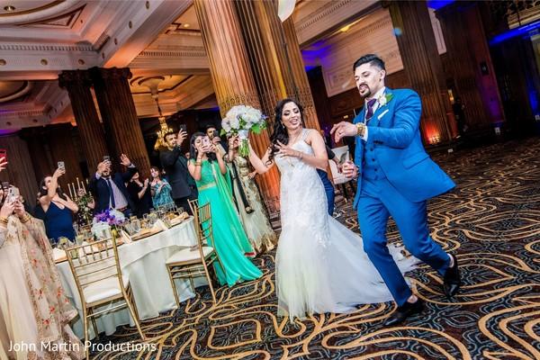Maharani and rajah walking in to wedding reception.