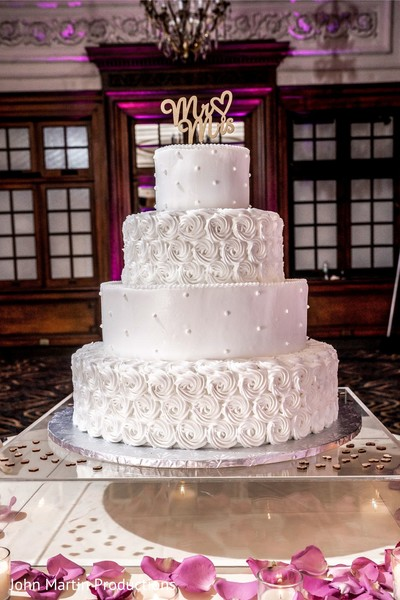 Indian white wedding cake with golden cake topper.