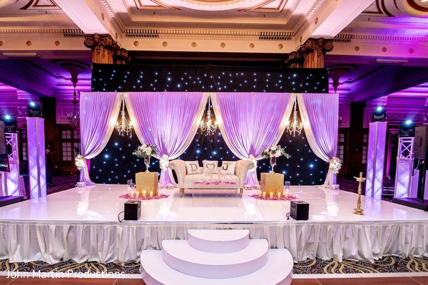 Indian wedding reception purple and white stage decorations.