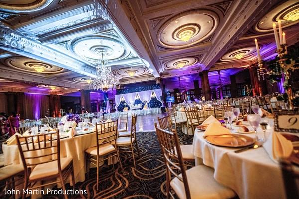 Indian wedding reception purple and blue lights decor.