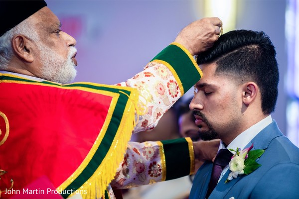 Indian groom being blessed at wedding ceremony.