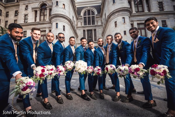 Indian groomsmen holding bridesmaids bouquet.