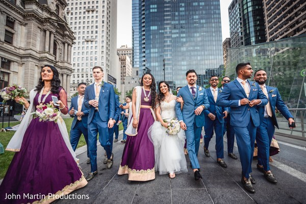 Indian couple walking outdoors on their wedding outfits.